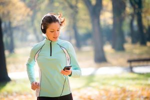 Young woman with headphones jogging listening to a podcast